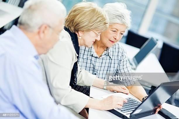 Teacher Explaining New Computer Technology to Senior Couple