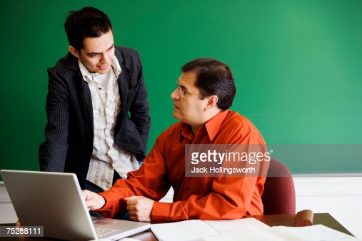 Teacher explaining student, using laptop : Stock Photo