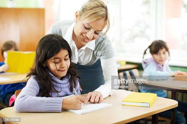 Teacher explaining tasks to a schoolgirl