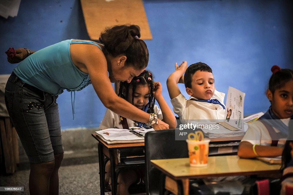 A teacher explains the lesson to a pupil, at a school in Havana on November 13, 2012.
