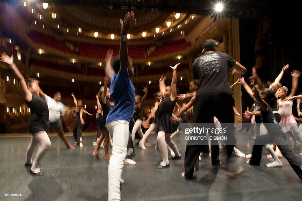 A teacher (R) from the Royal Opera House gives a classic dance class to children from Brazilian dance schools and from shantytowns, at the Municipal Theater in Rio de Janeiro, on February 23, 2013. The Royal Opera House of London landed in Rio this week with educational programs and events that include dance lessons for children living in the city's shantytowns. AFP PHOTO/Christophe Simon