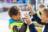 Teacher giving high-five to student outside kindergarten