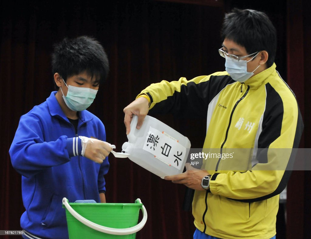 A teacher guides a student (L) on how to use disinfectant in a junior high school in Taipei on May 1, 2013. The deadly H7N9 bird flu strain claimed a new victim when a hospital patient died in China, state media reported, bringing the death toll from the recently identified virus to 24. AFP PHOTO / Mandy CHENG