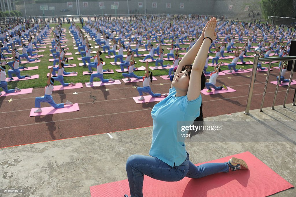 A teacher guides more than one thousand primary students to do yoga at a sports meeting in a primary school on April 29, 2016 in Jinan, Shandong Province of China. Different from former sports meetings in the school, it's said that every student became a real participant this time.