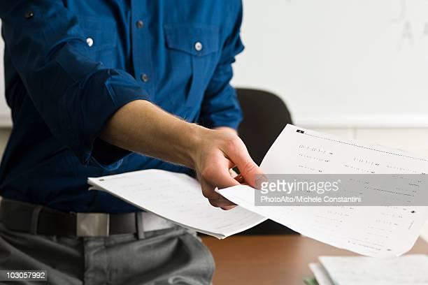Teacher handing out classwork assignment