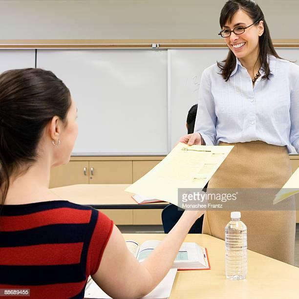 Teacher handing paper back to student