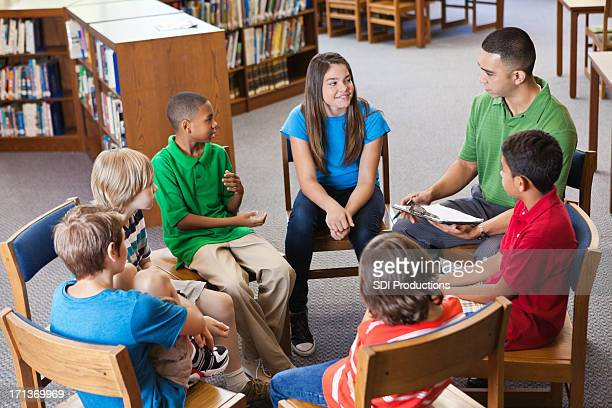 Teacher having discussion with students in library