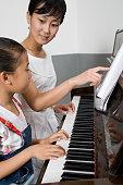 Professor ajudando um aluno jogar o piano