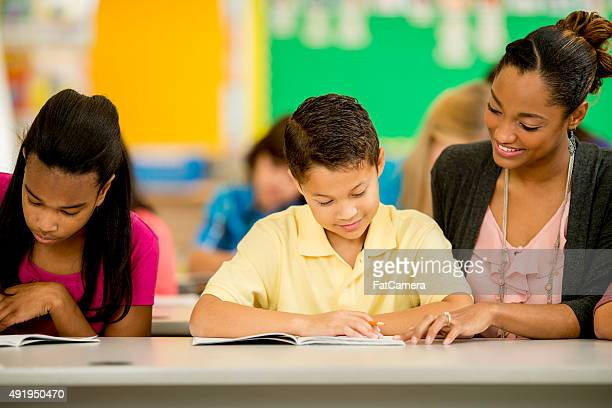 Teacher Helping a Student with a Reading Assignment