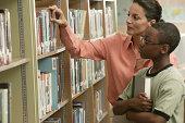 Teacher helping boy choose a book