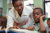 Teacher helping boy in classroom
