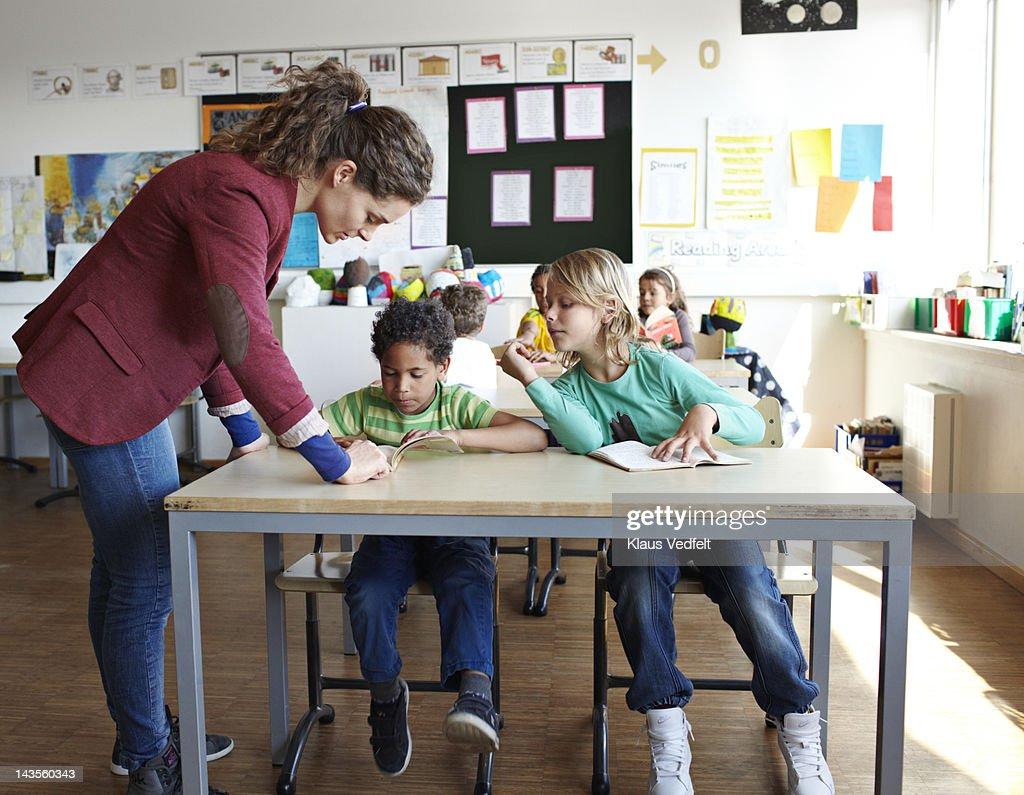 Teacher helping boy with reading