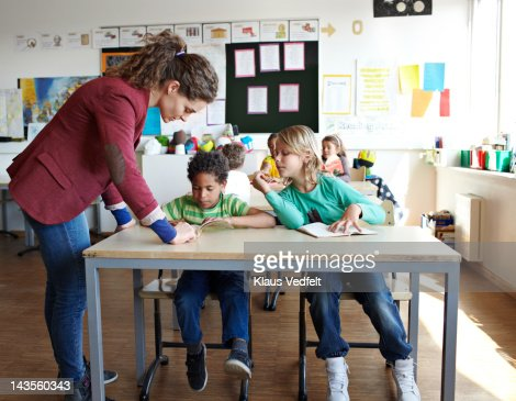 Teacher helping boy with reading