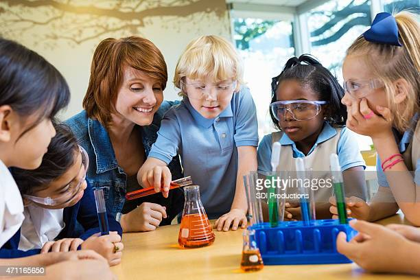 Teacher helping elementary students with science chemistry experiment