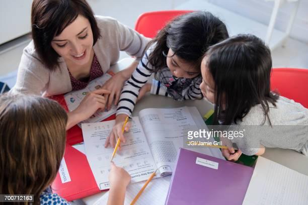 Teacher helping girls with workbook in classroom