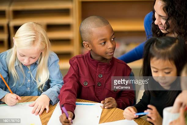 Teacher helping preschool student