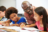 Teacher Helping Pupils Studying At Desks In Classroom Checking Work Smiling
