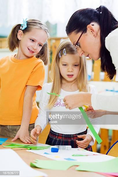 Teacher Helping Pupils With Artwork