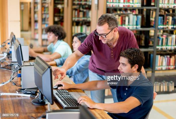 Teacher helping student at the library
