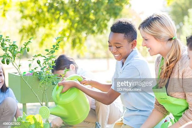 Professor ajudar aluno planta produtos hortícolas no jardim durante aula de ciências