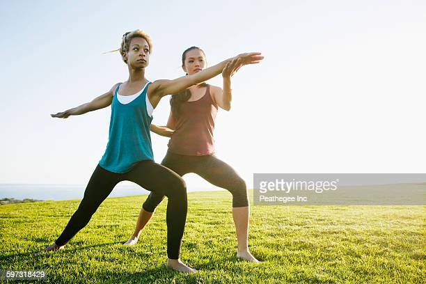 Teacher helping student practice yoga outdoors