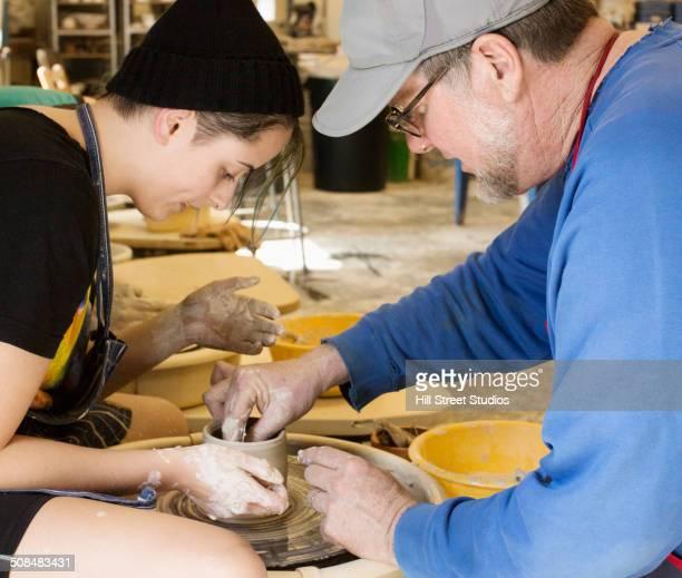 Teacher helping student throw pottery on wheel