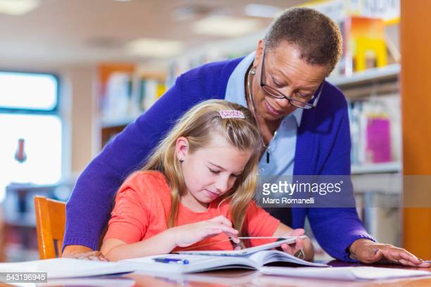 Teacher helping student use digital tablet in library
