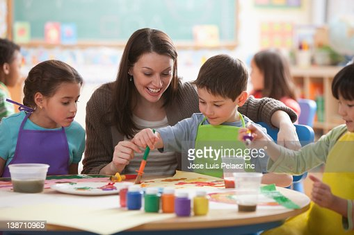Teacher helping students in art class : Stock Photo