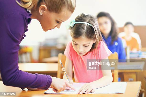 Teacher helping students in class.
