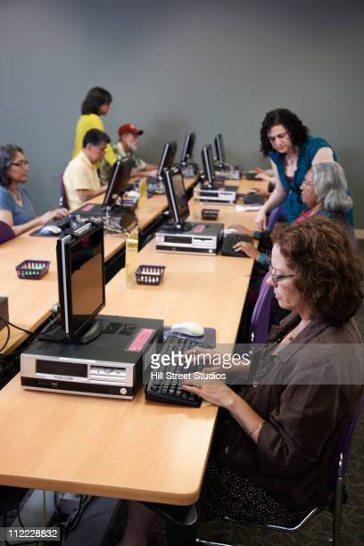 Teacher helping students on computers in computer lab