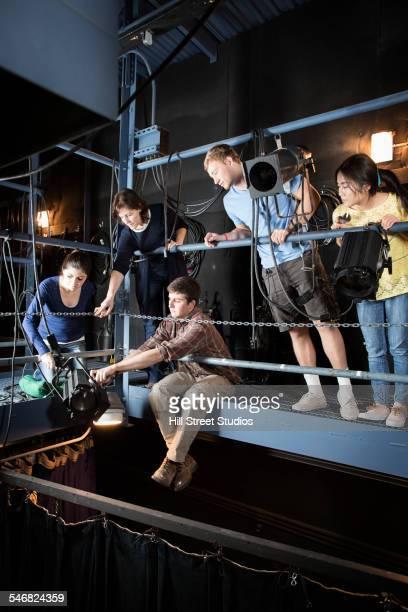 Teacher helping students organize theater lighting