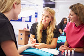Teacher Helping Students Training To Become Beauticians Painting Nails Smiling