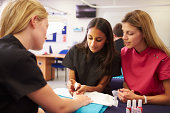 Teacher Helping Students Training To Become Beauticians Painting Nails