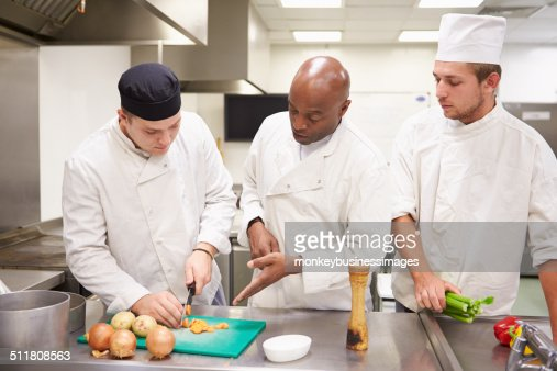 Teacher Helping Students Training To Work In Catering : Stock Photo
