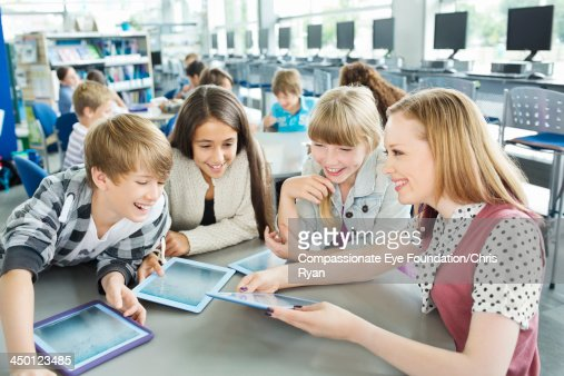 Teacher helping students with digital tablets