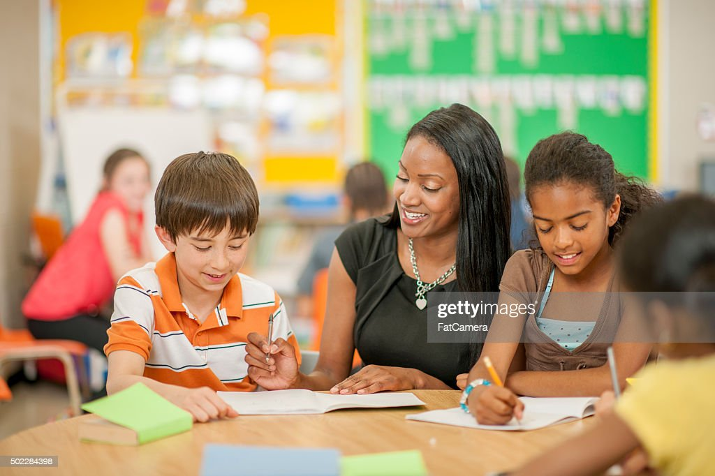 Teacher Helping Students with Questions : Stock Photo
