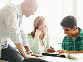 Teacher helping students working on digital tablet