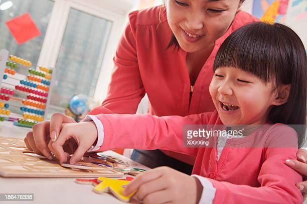 Teacher Helping Young Girl with Cut-Out Alphabet Letters