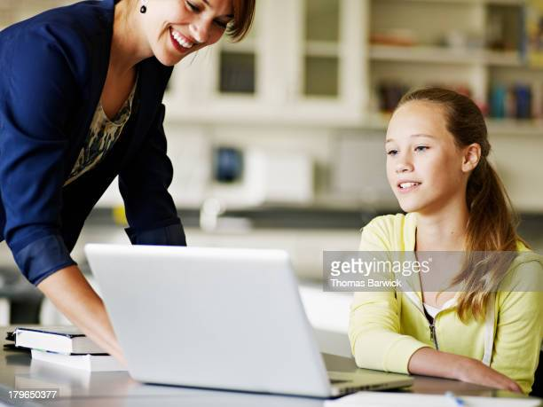 Teacher helping young student working on laptop