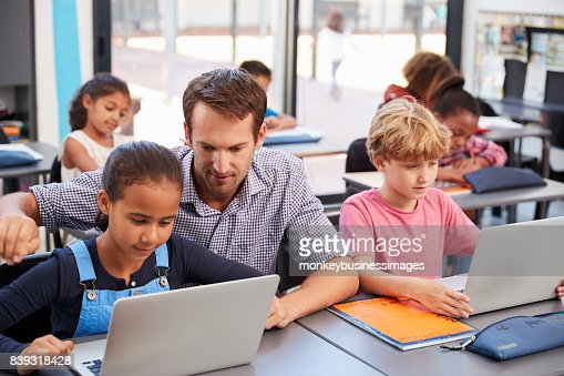 Teacher helping young students using laptops in class : Stock Photo