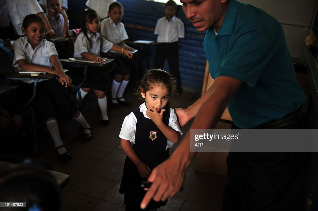 A teacher helps a schoolchildren at the Jean Paul Genie primary school during the year's first day of classes, in Managua, on February 11, 2013. AFP PHOTO/Hector RETAMAL