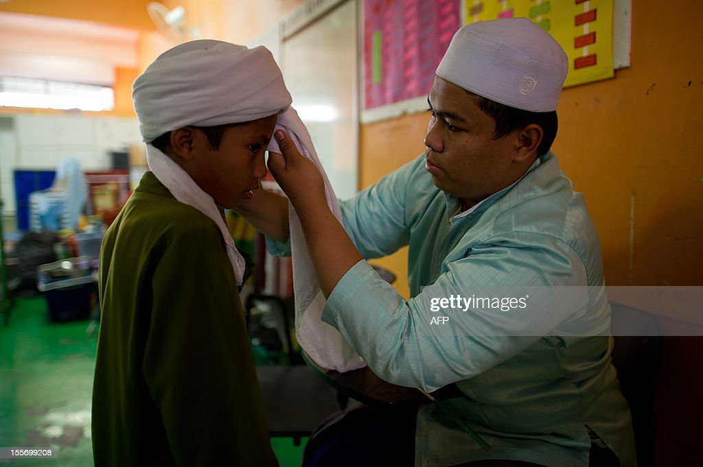 A teacher helps a student to wears turban at the Iqro Al-Quran Bestari academy for the orphanage in the suburbs of Kuala Lumpur on November 7, 2012.