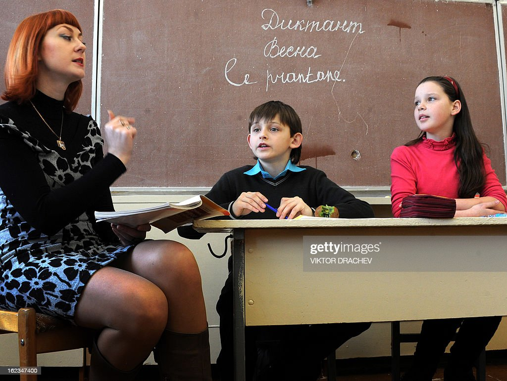A teacher helps her young students to learn French during a lesson at a secondary school in the Belarus town of Molodecho, some 85 km northwest of the capital Minsk, on February 22, 2013.