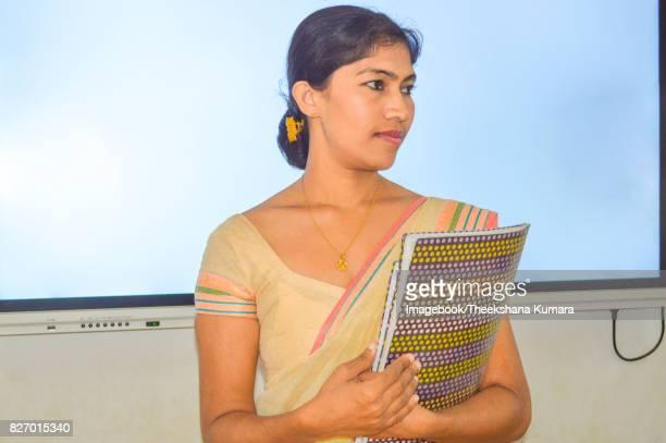 Teacher holding books in Smart classroom