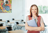 Teacher holding digital tablet in classroom