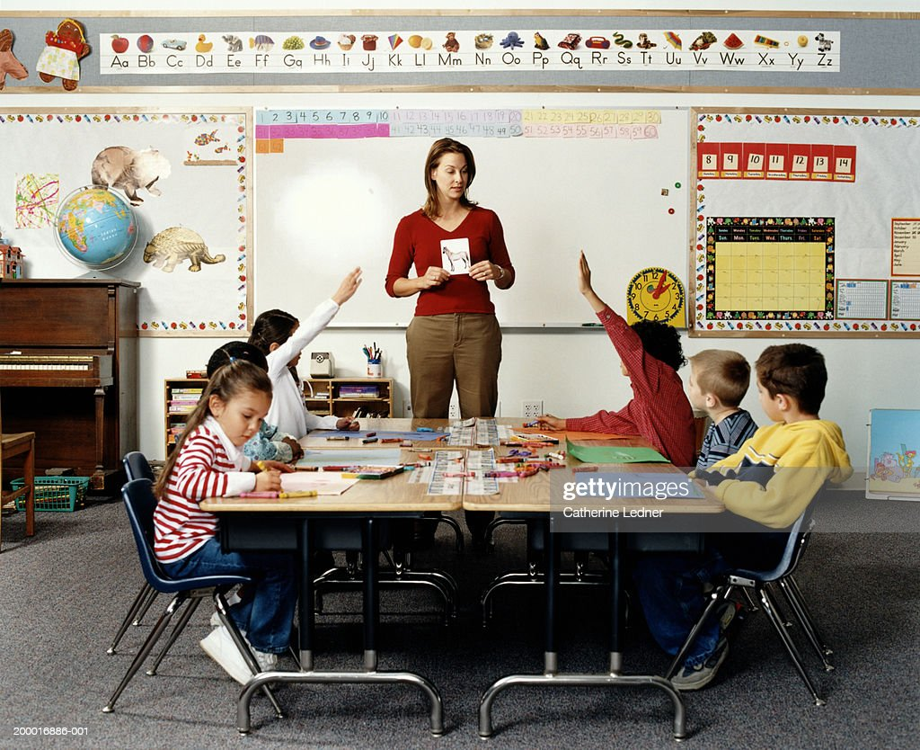 Teacher holding flashcard in front of children (5-7) : Stock Photo