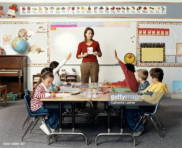 Teacher holding flashcard in front of children (5-7)