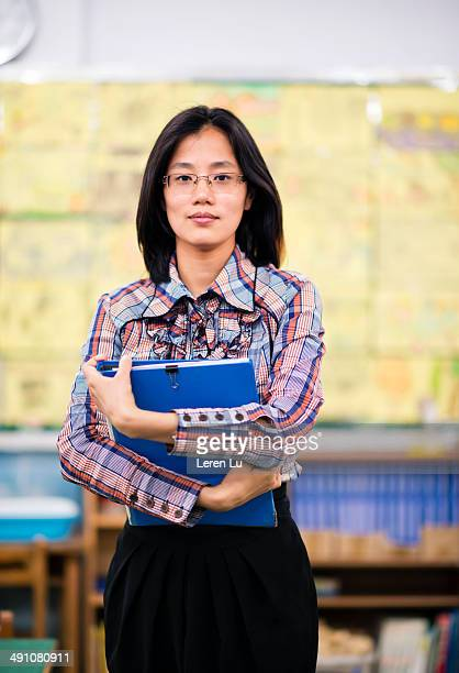 Teacher holding folder in classroom