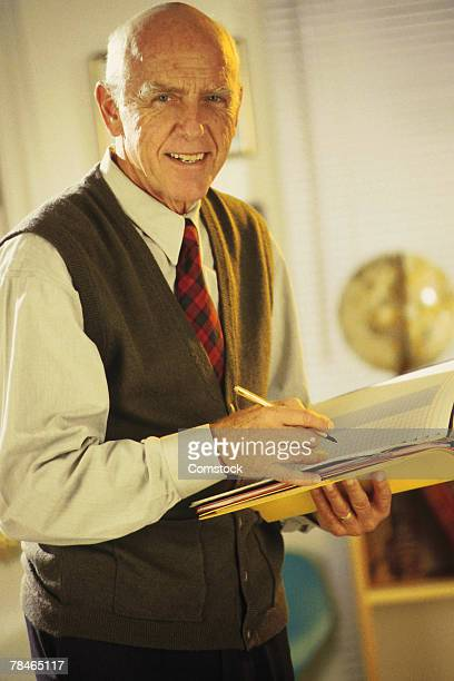 Teacher holding grade book and pencil