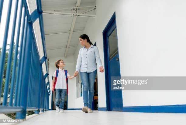 Teacher holding hands of a boy at the school